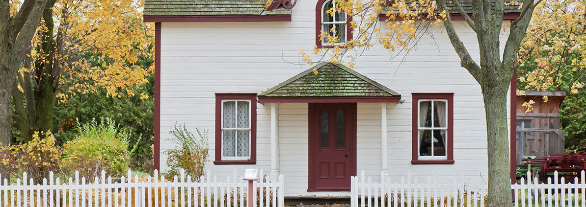 Older home with white paint, worn out roof and neglected landscaping that would benefit from exterior improvement projects with high ROI.